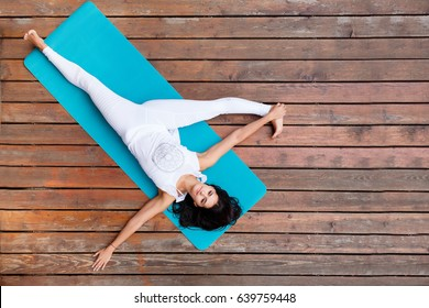 Top view of beautiful young fitness woman working out on wooden floor terrace, doing yoga exercise, full length