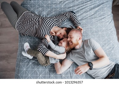 Top view of beautiful young mother, father and their daughter looking at camera and smiling while lying on bed head to head.