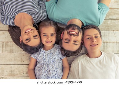 Top view of beautiful young parents, their cute little daughter and son looking at camera and smiling, lying on wooden floor
