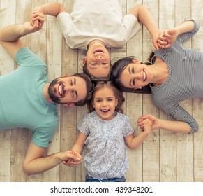 Top view of beautiful young parents, their cute little daughter and son holding hands, looking at camera and smiling, lying on wooden floor