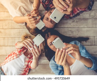 Top view of beautiful young parents and their children using smartphones and smiling while lying together on the floor at home