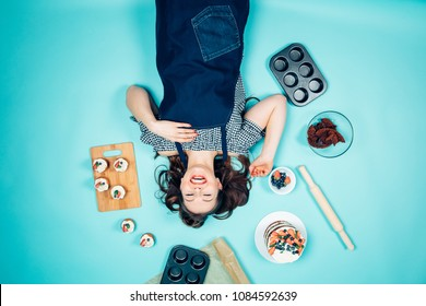 Top view of a beautiful young romantic woman lying on a blue background with confectionery , upside down