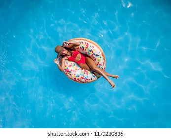 Top view of a beautiful young woman in swimming pool swims on inflatable ring donut and has fun on vacation.