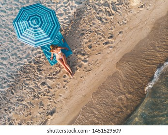 Top view of a beautiful young woman who is enjoying in sunbathe on the beach dressed in a bikini. She is relaxing on the blue beach towel under the blue umbrella.