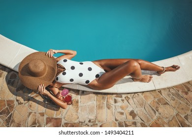 Top view of a beautiful young woman enjoying by swimming pool with glass of cocktail. She is lying down sunbathing, covered had with huge straw hat, near clear blue water.