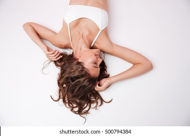 Top view of a beautiful young woman with long hair wearing white bikini isolated on the pink background