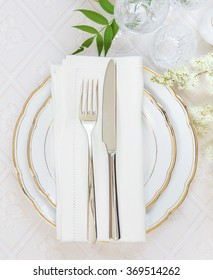 Top view of the beautifully decorated table with white plates, crystal glasses, linen napkin, cutlery and white flower on luxurious tablecloths