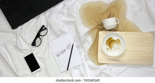 Top view of bed, notepad with black inscription wake up, notebook, smart phone, glasses, spilled coffee from white cup on wood board. Home working mock up. How hard to get up in the morning concept