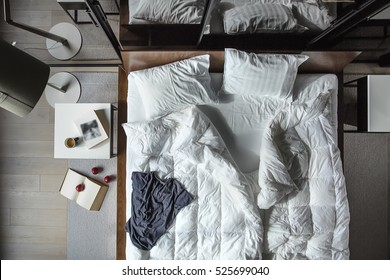 Top view at the bed with white pillows and blankets and blue T-shirt. There are white tables, lamp with lampshade, wardrobe with glass sliding doors. On the floor there is carpet with book and apples.