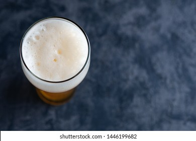 Top view of beer glass with foam cap and copyspace