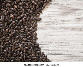 Top view - Beer ingredients, Chocolate malt on wooden background ( Space and composition for text )