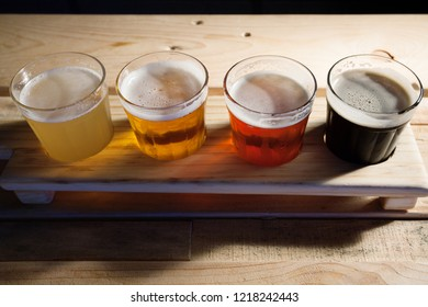 Top view of Beer samplers in small glasses individually placed in holes into a unique wooden tray and background. Amazing light.