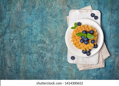 Top view of belgian waffles with fresh blueberries on blue concrete background with copy space