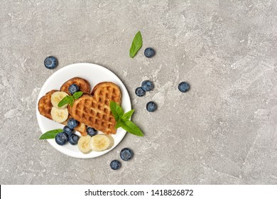 Top view of belgian waffles with fresh blueberries and bananas on gray concrete background with copy space
