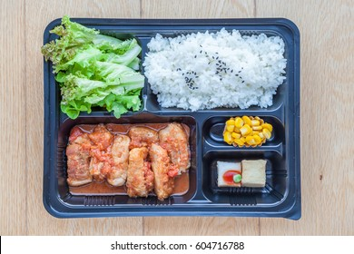 Top view of bento to-go plastic box, streamed Japanese rice with teriyaki grilled chicken in tomato sauce in lunch box place on wooden board background.