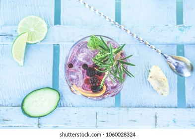Top view of berries mojito cocktail on blue wood bar counter - Tropical, drinks, party and concept - Focus on glass
