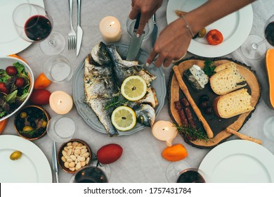 Top view of best friends dining together by candle, Mediterranean Kitchen Healthy Food, Holidays Celebrate Summer Dinner Party Concept, Woman cutting freshly cooked dorado fish with rosemary and lemon