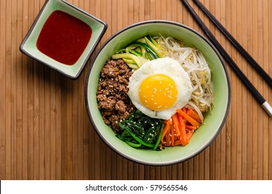 Top view of Bibimbap, a classic Korean meal. Rice is topped with seasoned vegetables, meat and a sunny side up fried egg on top. Spicy chili sauce can be added to finish off this savoury Asian dish.