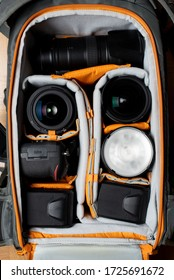 Top view of a big photography backpack showing the DSLR gear. A camera body, few lenses and lighting equipment symmetrically positioned.