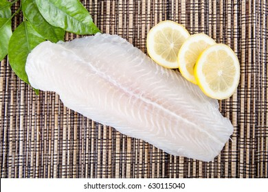 Top view Big slice of fish raw food with lemon and green leaf