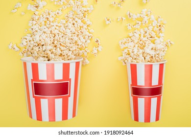 top view of big and small buckets with tasty popcorn on yellow, cinema concept