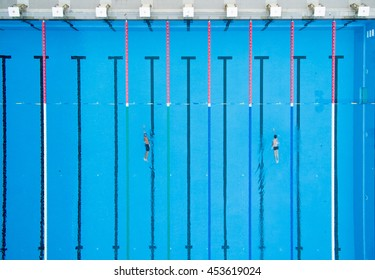 Top View, Bird Eye View of Blue Swimming Pool with Swimmers and Starting Platforms.