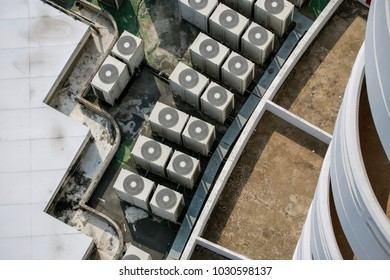 top view or bird eye's view of top terrace platform of skyscraper building in urban area with air condition hot coil condensing, many hot air pollution from air condition cause global warming concept