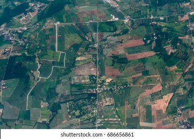 Top view or bird's-eye view of ground landscape with fertile soil and grass land in green and brown color. It is an aerial photograph taken from a plane showing an elevated view from above like a map.