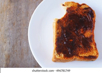 Top view of a bite out of a vegemite sandwich on a wooden table.