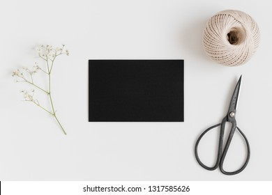 Top view of a black card mockup with a gypsophila and workspace accessories on a white table.