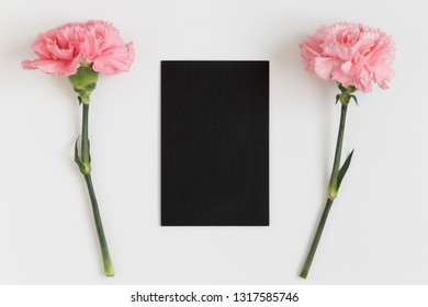 Top view of a black card mockup with pink carnations on a white table.