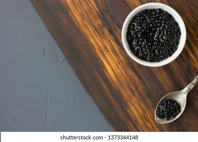 Top view of black caviar in a metal spoon.