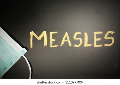 Top view of a black chalkboard with the medical phrase Measles written on it with chalk and a green or blue medical face mask. Measles outbreak, vaccination or epidemic concept