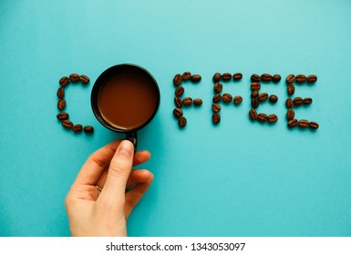 """Top view of black coffee and  beans on blue background with copy space, banner style for text. Coffee Beans Background. Flat lay composition. """"Coffee"""" word made of coffee beans."""