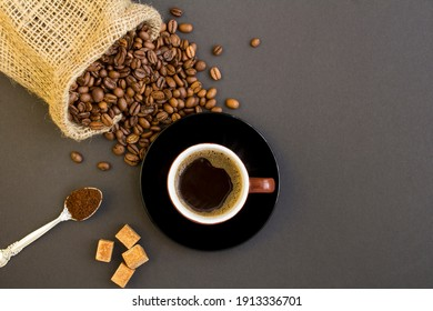 Top view of black coffee in the brown cup and coffee beans on the dark background