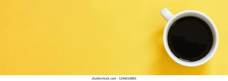 Top view of black coffee cup on yellow background with copy space, banner concept for text