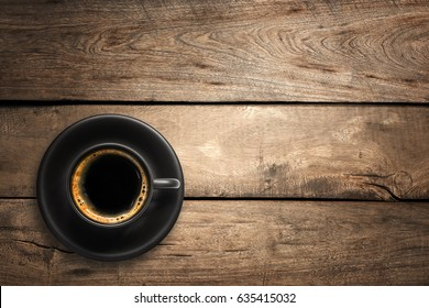 Top view of a black coffee cup on wood background.