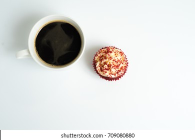 Top view of black coffee cup with a red velvet cupcake on top left corner in white background