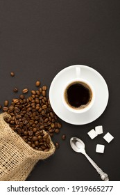 Top view of black coffee in the white cup and coffee beans on the dark background