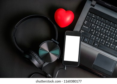 Top view of black color gadget headphone smart phone laptop and red heart rubber model.image with copy space