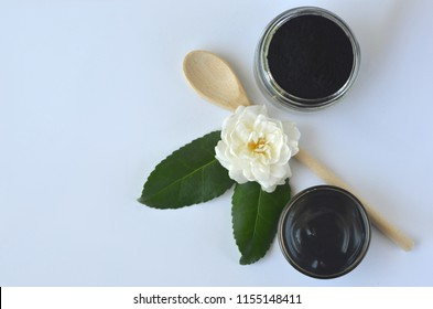 Top view of black cosmetic activated charcoal powder and beauty face mask  mixture on white. Oily skin, detox and acne treatment.