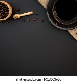 Top view a black cup of coffee americano and coffee bean grain on sack fabric put on black wood table background include copyspace for add text or graphic