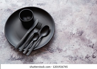Top view of black empty round plate and tableware on marble stone background