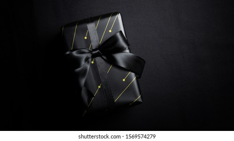 Top view of black gift box with black ribbons isolated on black background. Shopping concept boxing day and black Friday sale composition.