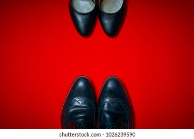 49216fae61 Top view of black high heels and men s shoes on an intense red background. four  pair of ...