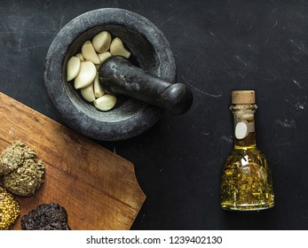 Top view of black mortar and pestle with fresh pieces of garlic inside. Bottle of olive oil with spices. Wooden cutting board with three types of sauces, including french mustard on black chalkboard.