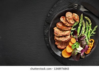 Top view of a black plate with fried slices of beef, sweet potato and mixed salad on black slate stone