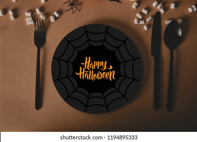 "top view of black plate with spider web and ""happy halloween"" lettering, fork and knife with marshmallows on table"