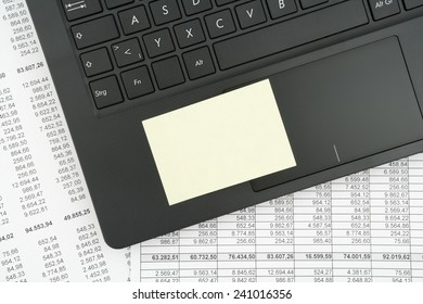top view of black textured laptop keyboard with post it note on white documents with numbers