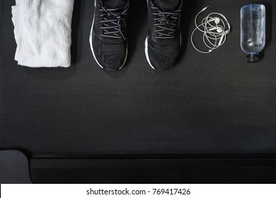 Top view of black tone fitness accessories  on treadmill background with copy space, running concept
